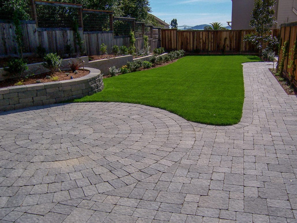 driveway with pavers with grass alongside of it